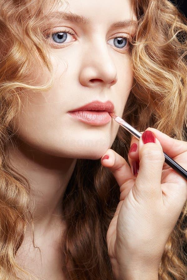 Make-upkunstenaar die visagiste borstel voor toepassingslippenstift gebruiken op lippen van jong Kaukasisch model met golvend gem stock fotografie