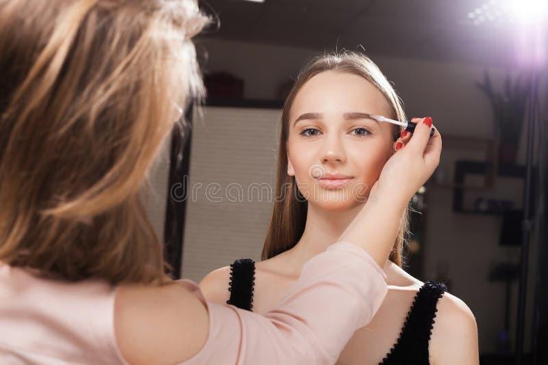 Make-upkunstenaar het borstelen wenkbrauwen van een cliënt royalty-vrije stock afbeeldingen