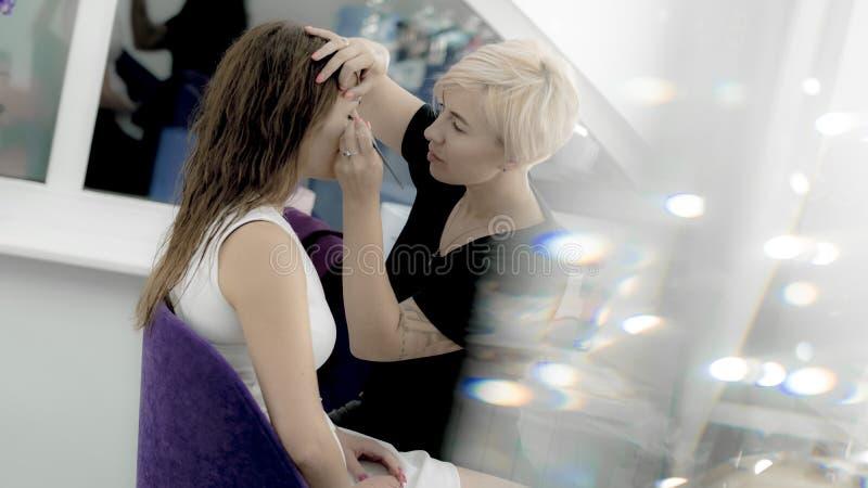 Make-upkunstenaar het schilderen ogen van mooi model royalty-vrije stock afbeelding