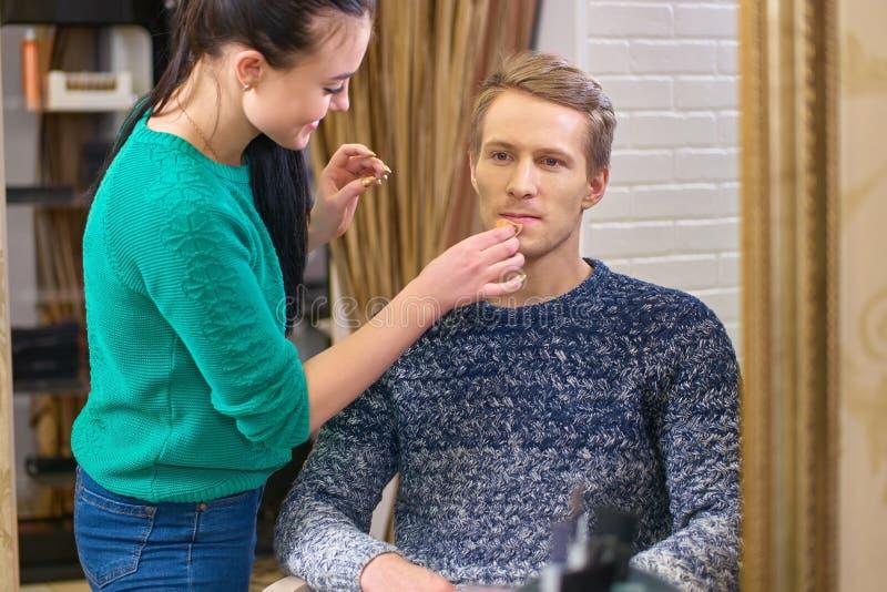 Make-upkunstenaar, jong mannelijk model stock fotografie