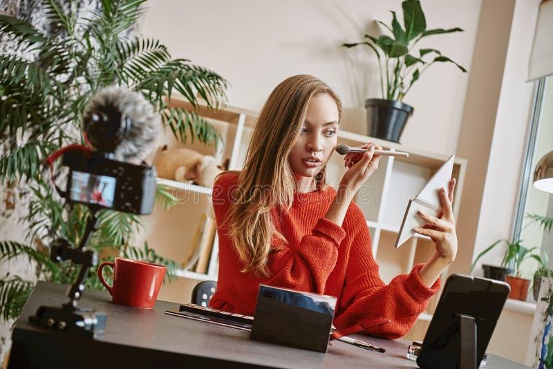 Make-upleerprogramma Leuke en jonge blogger die toe te passen borstel gebruiken highlighter terwijl het uitzenden van levende vid royalty-vrije stock foto's