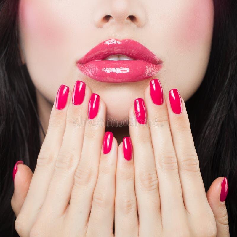 Make-uplippen mit rosa Lippenstift, Lipgloss und Maniküre stockfotos