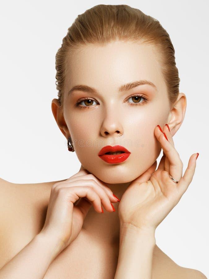 Make-upproducten Jong mooi meisje met gouden oorringen en ring die op witte achtergrond glimlacht Rode spijkers met manicure stock foto