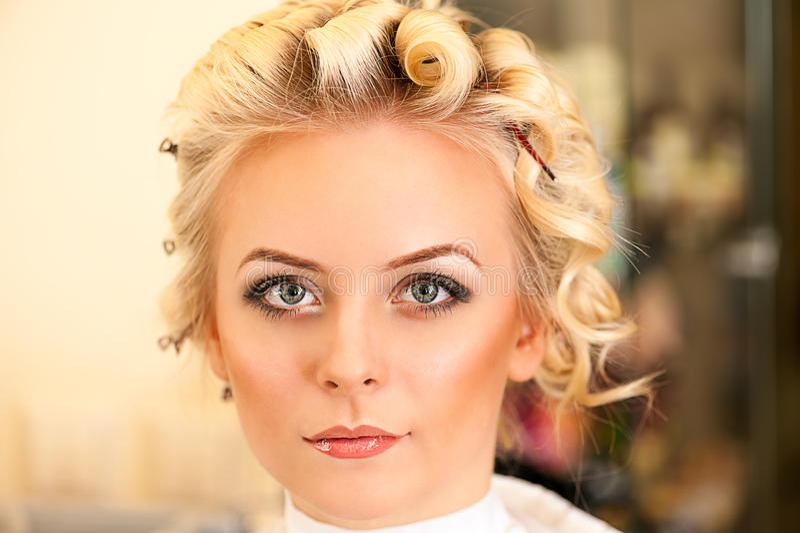 Make-upvrouw in een schoonheidssalon stock afbeeldingen