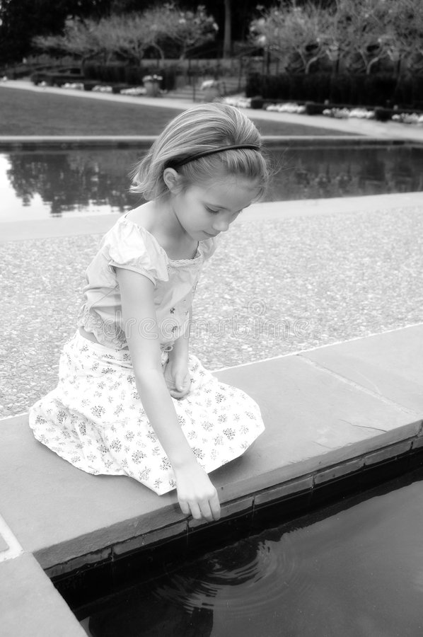 Make a wish. Little girl drops a penny into a fountain of water. Black and white royalty free stock photography