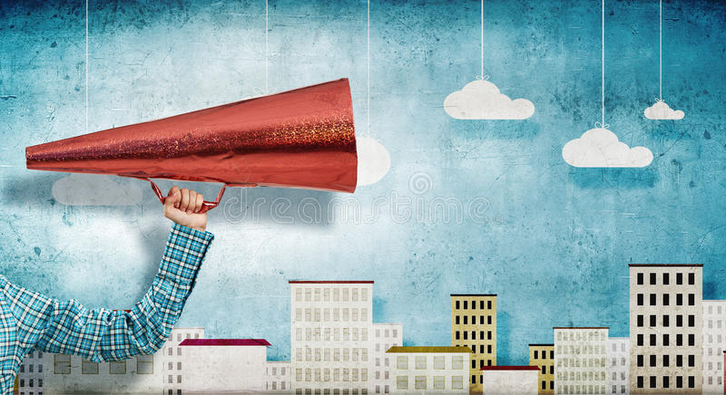 Make your announcement . Mixed media. Close of hand holding red paper trumpet royalty free stock photo