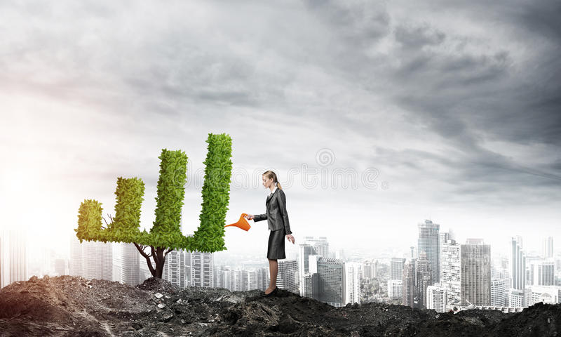 Make your money grow. Young attractive businesswoman watering symbol chart plant in ground with can against the backdrop of the city stock photos
