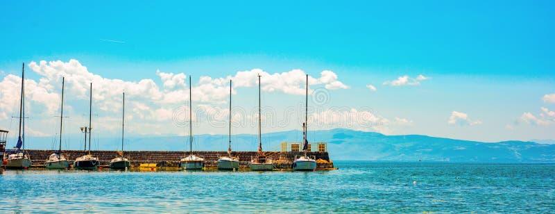 Makedonia północna. Ochryda. Długi molo z różnymi szybowcami i górami na tle fotografia stock