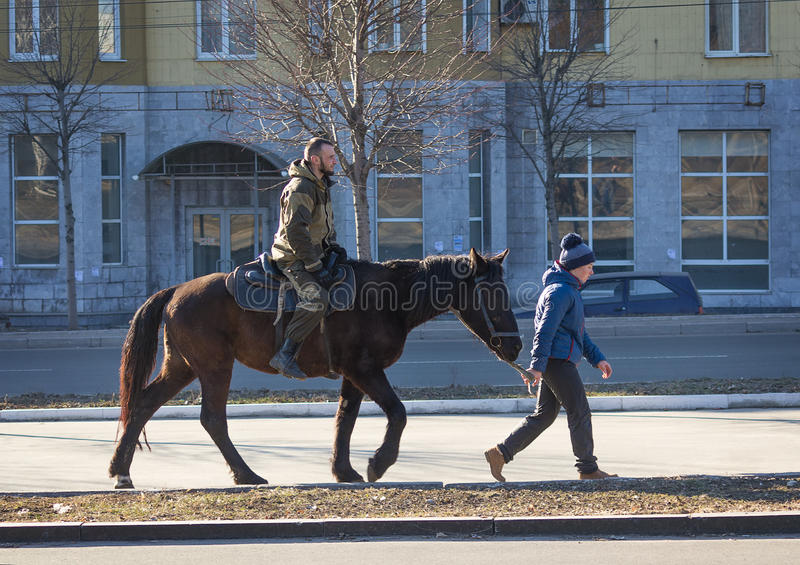 Makeevka, de Oekraïne - Februari, 22, 2015: Jongensrit een Volksrepubliek van loshadisoldatadonetsk tijdens de vakantie van Shrov stock afbeelding