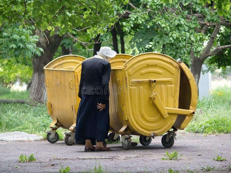 Makeevka, Ucrânia - 29 de maio de 2015: Uma mulher idosa perto de um garbag imagens de stock royalty free