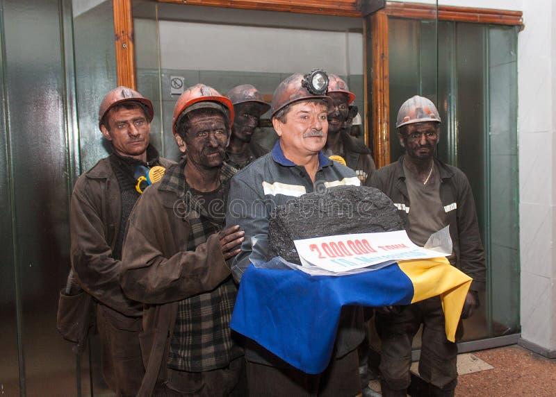 Makeevka, Ucrânia - 26 de novembro de 2013: Mineiros com o lingote simbólico de carvão fotografia de stock