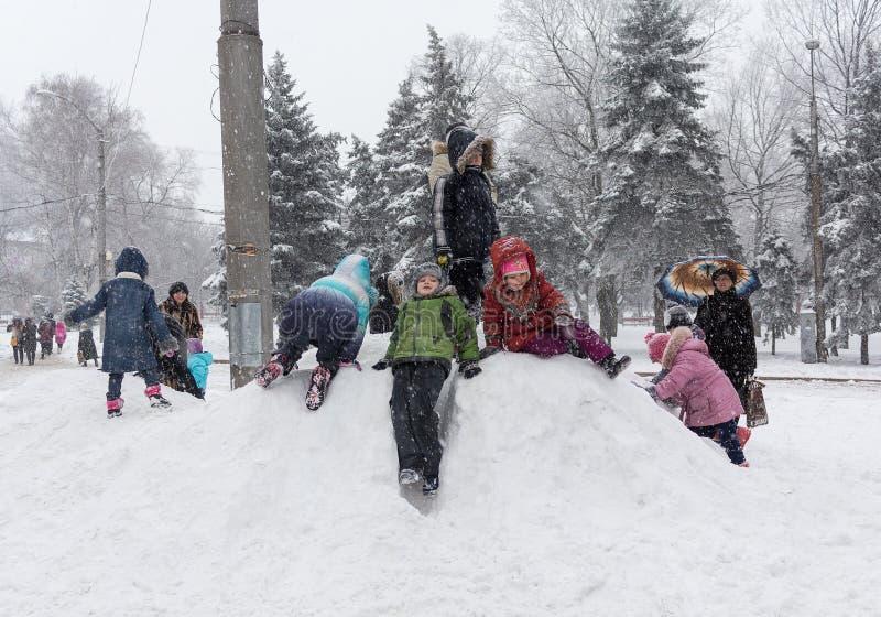 Makeevka Ukraina - Januari 07, 2016: Makeevka Ukraina - Januari 07, 2016: Barn som spelar på en snöig kulle på en central fyrkant royaltyfri fotografi