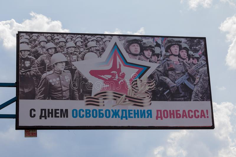 Makeevka, Ukraine - August 24, 2017: Banner on a city street depicting soldiers of the Red Army and fighters of the self-proclaime royalty free stock image