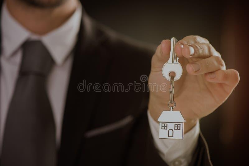 Makelaar in onroerend goed die huissleutel aanbieden royalty-vrije stock foto's