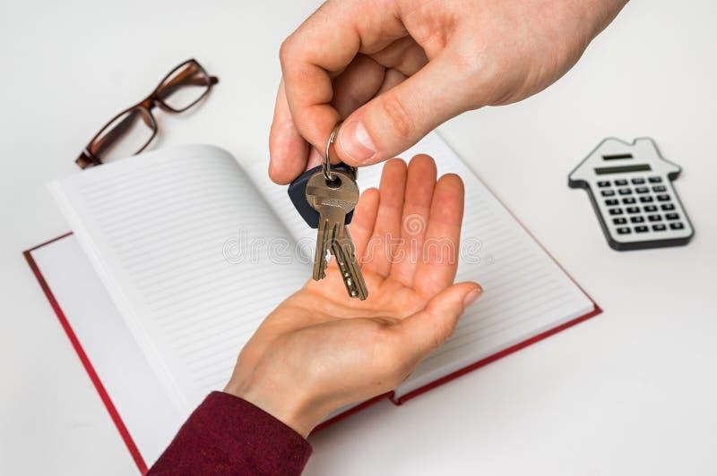 Makelaar in onroerend goed die sleutels van nieuw huis geven aan jonge vrouw royalty-vrije stock foto