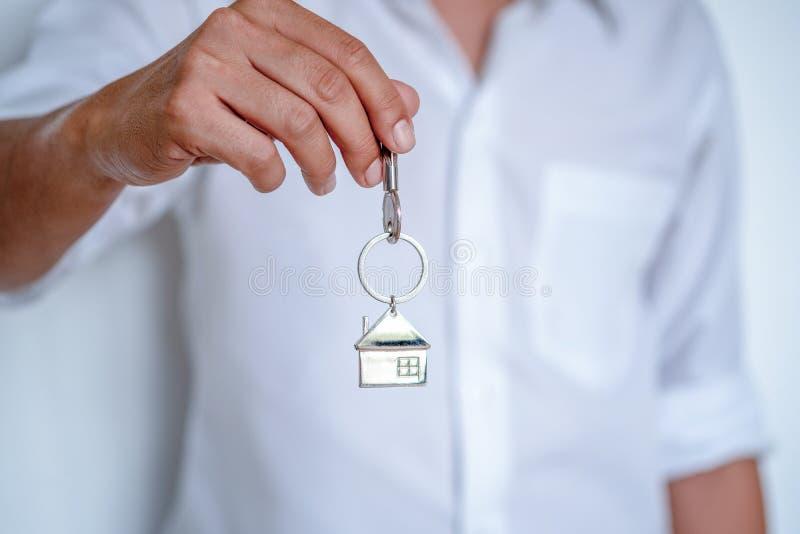 Makelaar in onroerend goed het overhandigen de huissleutels, de holdingssleutel van de Mensenhand met gevormd huis keychain, slui stock afbeelding