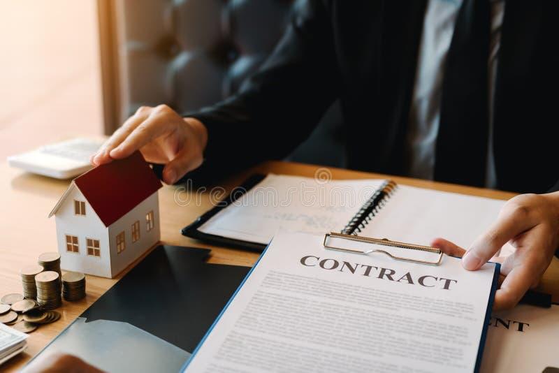 Makelaar in onroerend goedbespreking over het ondertekenen over document financieel contract bij bureauagentschap stock fotografie