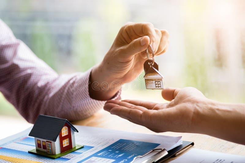 Makelaar in onroerend goedholding het indienen sleutels tot klant na het ondertekenen van het contract van verkoop inkoopovereenk royalty-vrije stock afbeeldingen