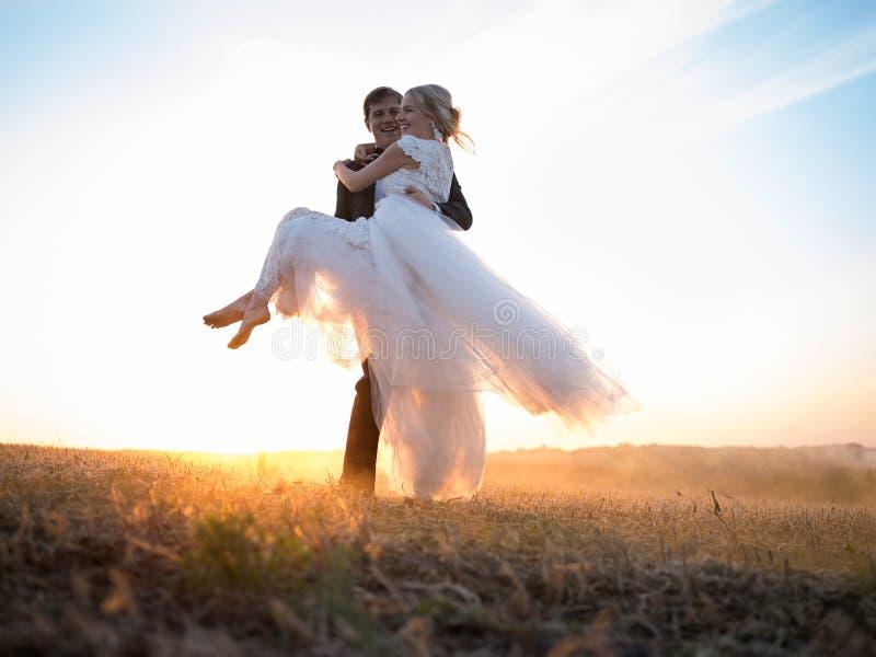 Maken bär hans älskade fru i hans armar, i inställningssolen royaltyfri foto