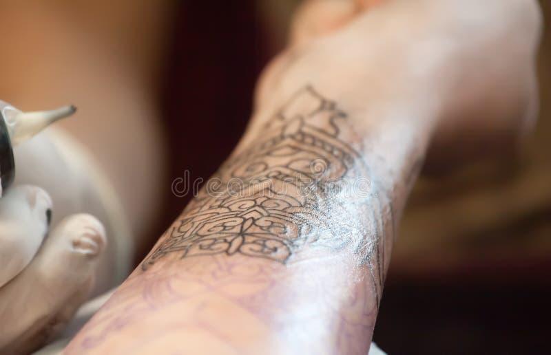 Maken de tatoegerings hoofd beschermende handschoenen een tatoegering in zwarte inkt op de hand stock fotografie
