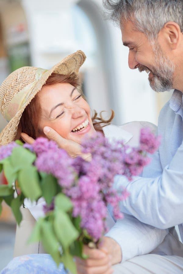 Maken förvånar hans fru med en bukett av lilor fotografering för bildbyråer