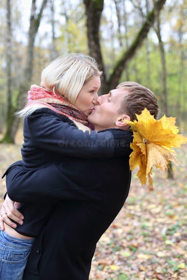 Maken och frun omfamnar och kysser i höstskog. arkivbild