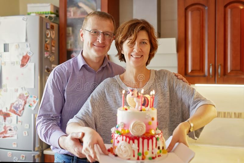 Maken och frun rymmer en kaka med stearinljus royaltyfri bild