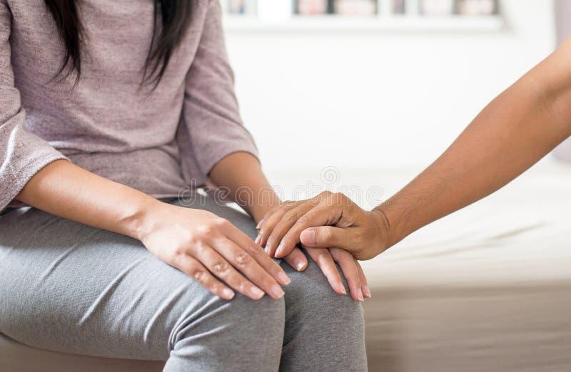 Maken som ger handen till deprimerat hans fru för, uppmuntrar hemma, det Meantal hälsovårdbegreppet arkivfoto