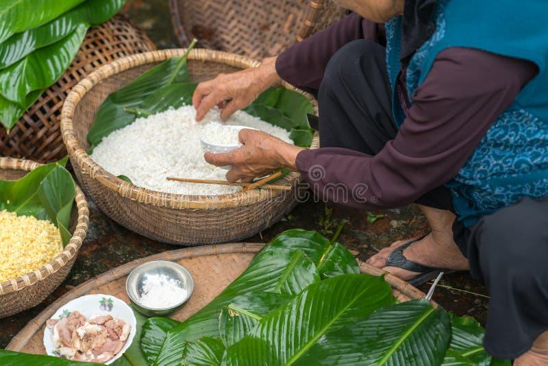 Makend verpakkend Chung Cake, het Vietnamese maan nieuwe voedsel van jaartet openlucht met oude vrouwenhanden en ingrediënten slu royalty-vrije stock afbeeldingen