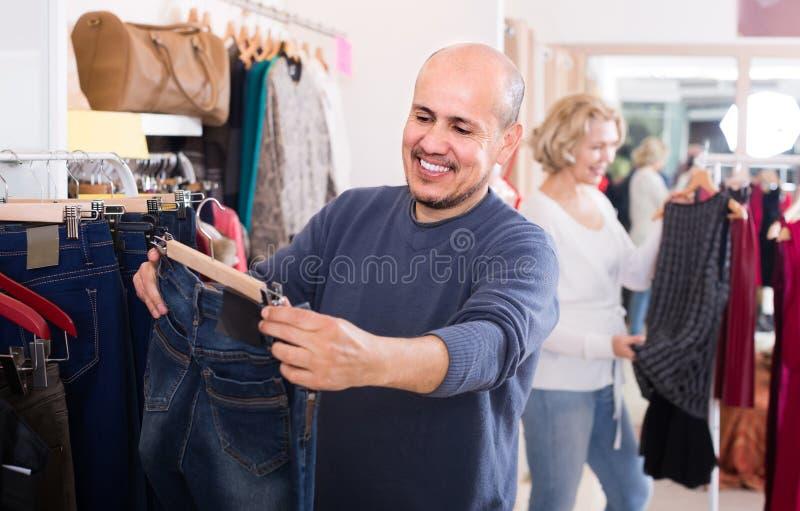 Maker som köper par av klassisk jeans i boutique royaltyfri bild