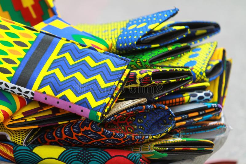 A makeshift stall kente cloth wallets at a street market in Accra, Ghana. In vibrant, vivid, colors of red, blue green, yellow, orange royalty free stock image