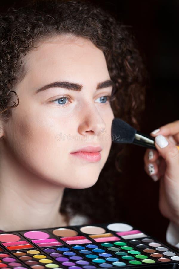 Makeup που εφαρμόζει την κινηματογράφηση σε πρώτο πλάνο Καλλυντική βούρτσα σκονών Πορτρέτο της όμορφης γυναίκας που παίρνει την ε στοκ φωτογραφία με δικαίωμα ελεύθερης χρήσης