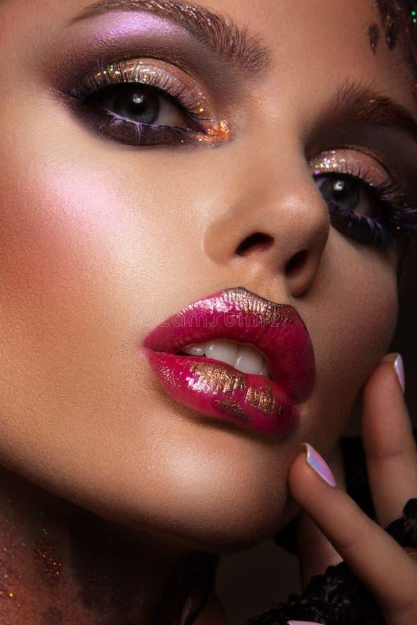 Το πρότυπο μόδας με το φωτεινό makeup και ζωηρόχρωμος ακτινοβολεί στοκ εικόνες