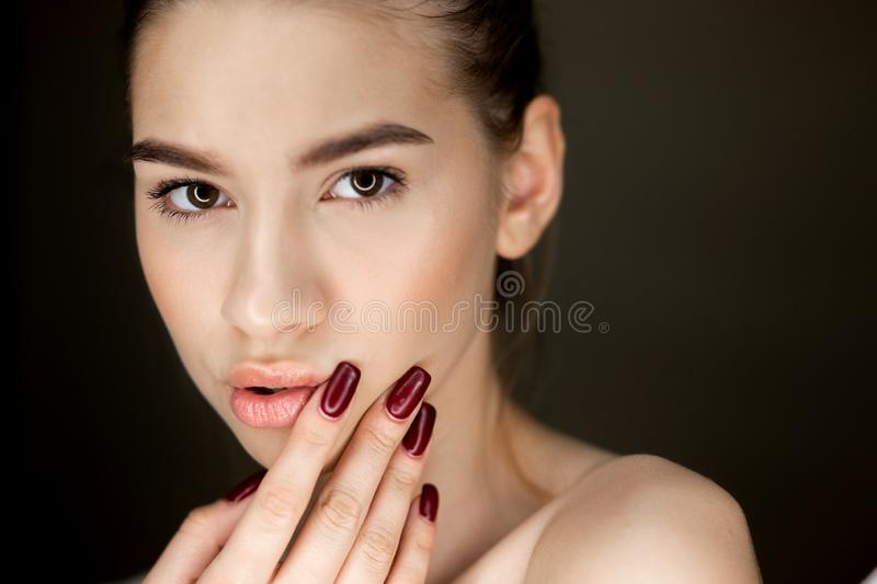 Πορτρέτο του νέου καφετής-μαλλιαρού κοριτσιού με το φυσικό makeup που κρατά τα δάχτυλά της στο πρόσωπό της στοκ εικόνα με δικαίωμα ελεύθερης χρήσης