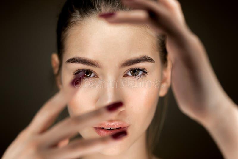 Πορτρέτο του νέου όμορφου καφετής-μαλλιαρού κοριτσιού με το φυσικό makeup που κρατά τα δάχτυλά της μπροστά από το πρόσωπό της στοκ εικόνες με δικαίωμα ελεύθερης χρήσης