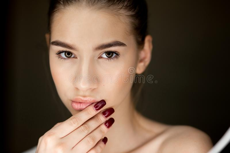 Πορτρέτο του νέου καφετής-μαλλιαρού κοριτσιού με το φυσικό makeup που κρατά τα δάχτυλά της στο πρόσωπό της στοκ φωτογραφία με δικαίωμα ελεύθερης χρήσης
