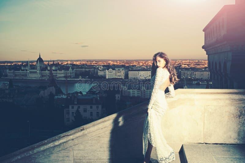 Γυναίκα στο άσπρο γαμήλιο φόρεμα στην άποψη πόλεων βραδιού, μόδα Αισθησιακή γυναίκα με μακρυμάλλη στο μπαλκόνι, ομορφιά Νύφη με στοκ φωτογραφία με δικαίωμα ελεύθερης χρήσης