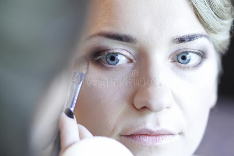 Makeup. Portrait of blond woman with blue eyes applying makeup stock photo