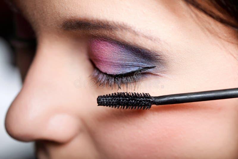 Makeup. Applicera mascara. Långa ögonfrans arkivfoton
