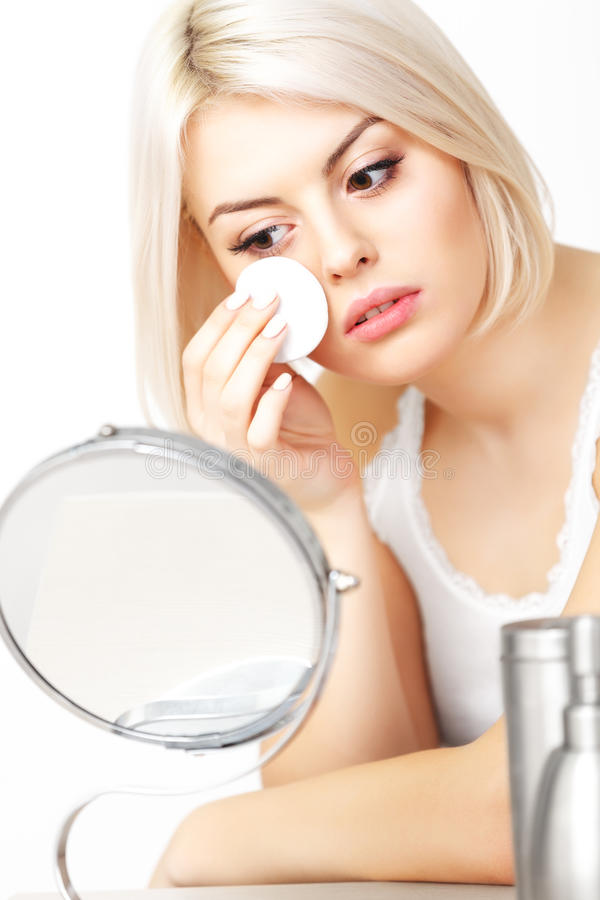 Makeup Applying. Beautiful Woman Looking at Her Face in the Mirror applying Cosmetic Sponge royalty free stock photography