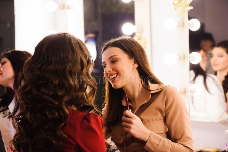 Makeup artist applies lipstick. Beautiful woman face. Perfect makeup. stock image