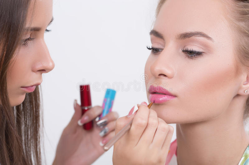 Makeup artist applies lipstick. Beautiful woman royalty free stock photo