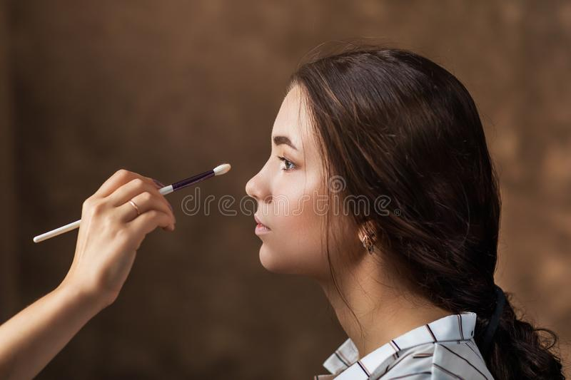 Makeup artist applies nude makeup to emphasize the natural beauty of the girls face stock images