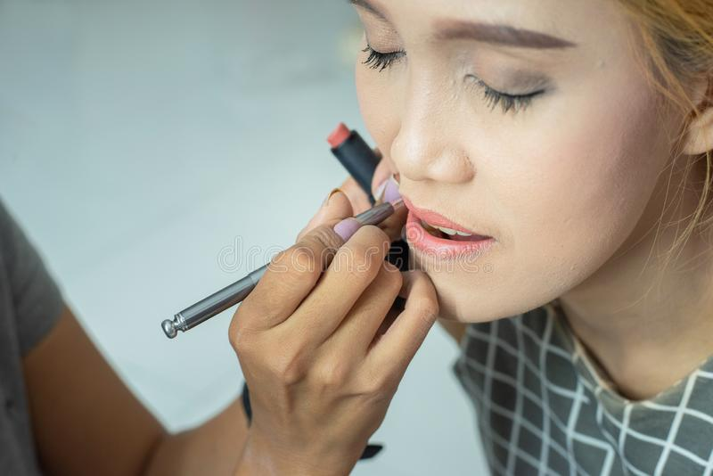 Makeup artist applies red lipstick . Beautiful woman face. Hand of make-up master, painting lips of young beauty asian model girl royalty free stock image