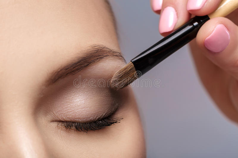 Makeup artist apply makeup brush for eyes. makeup for young girl. brown eye shadow. close up royalty free stock image