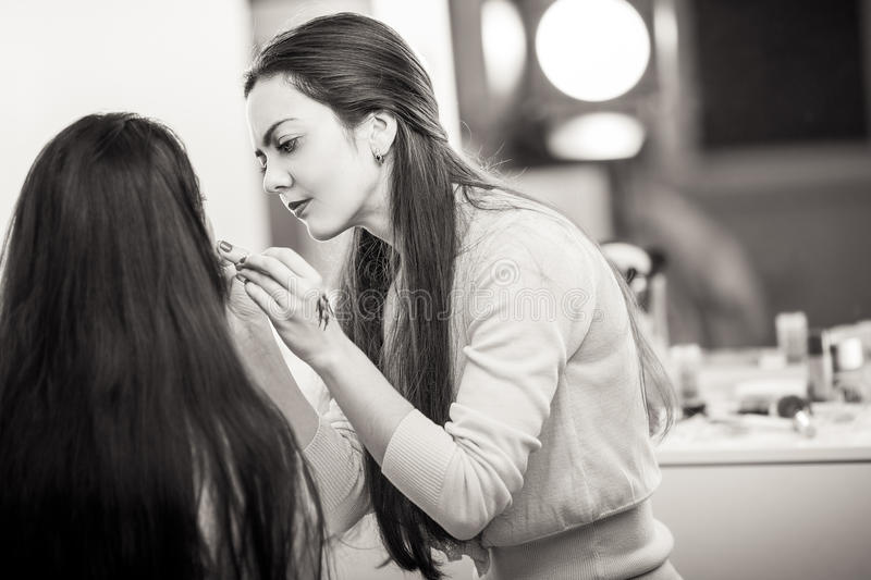 Makeup artist apply makeup. To a model royalty free stock images