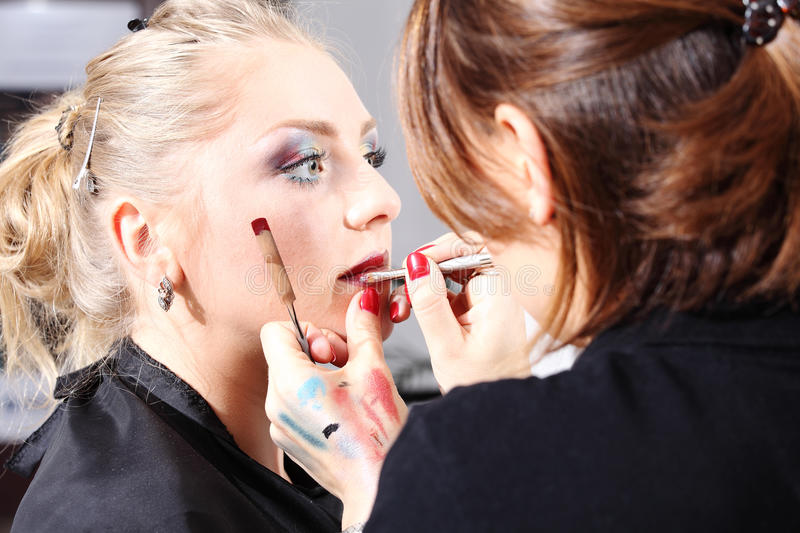 Makeup artist applying lipstick on model lips stock photos