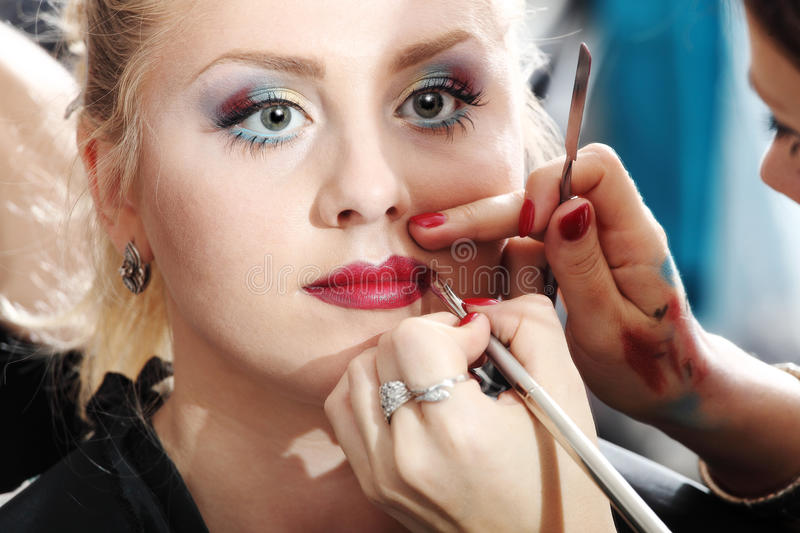 Makeup artist applying lipstick on model lips royalty free stock photos