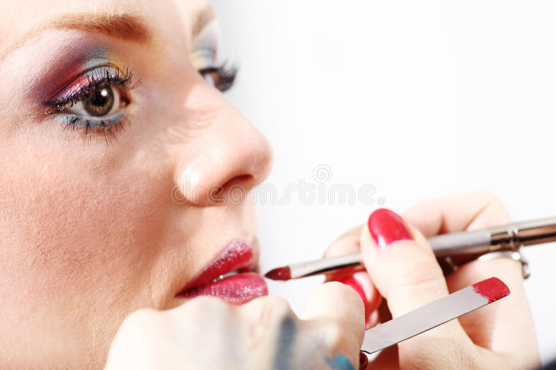 Makeup artist applying lipstick on model lips with brush royalty free stock photo