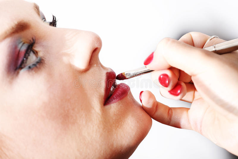 Makeup artist applying lipstick on model lips with brush royalty free stock photography